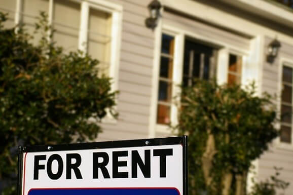 A For Rent sign in front of a white house near where Realty Medics offers Orlando home rentals