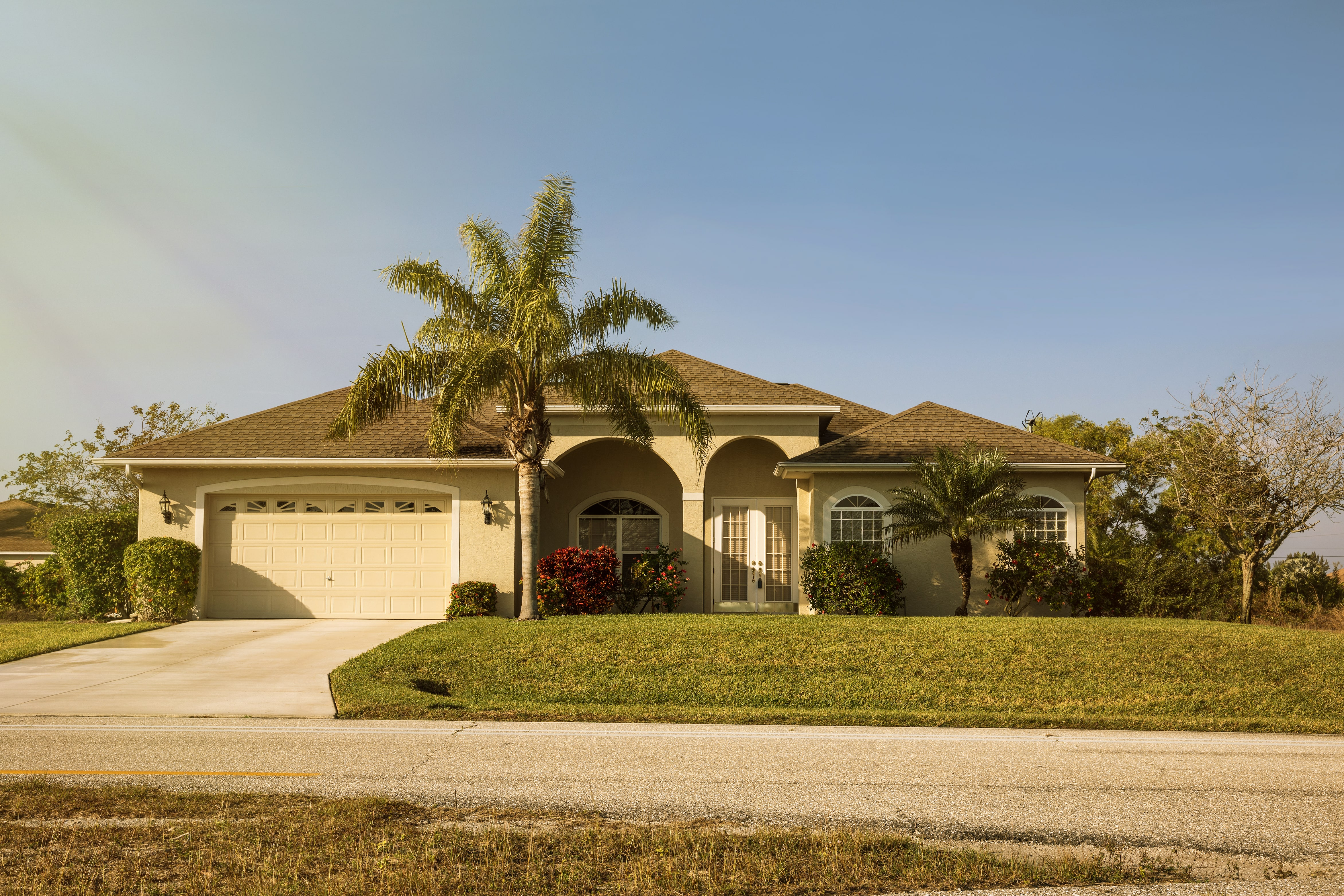 A light yellow house with a large green lawn and palm tree, near where homeowners can find Deltona property management