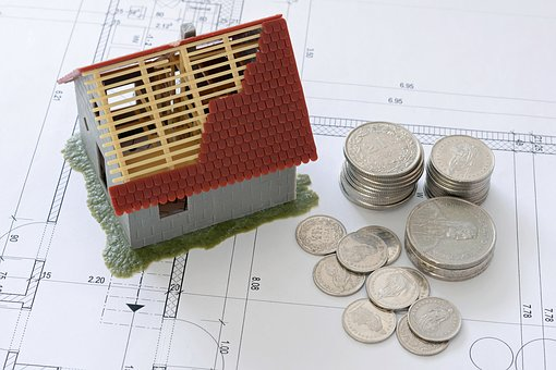 A miniature house and pile of coins on top of a blueprint paper