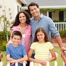 A family with a mother, a father, and two children, standing and smiling in front of a beige house with a green lawn, near where Realty Medics provides Lakeland property management